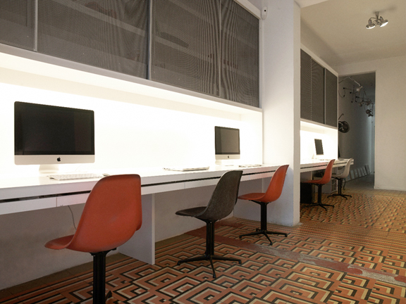 YSLANDIA AGENCY Madrid 2009.  A high efficiency interiors renovation for a communications agency. Two main open spaces within a classic turn of the century apartment were linked via the integration of custom built programmatic walls containing work posts, storage and cable management units. . Existing classic finishes including tile floors and ceiling moldings were maintained to contrast against the modern work units thus maintaining overall cost to a minimum.